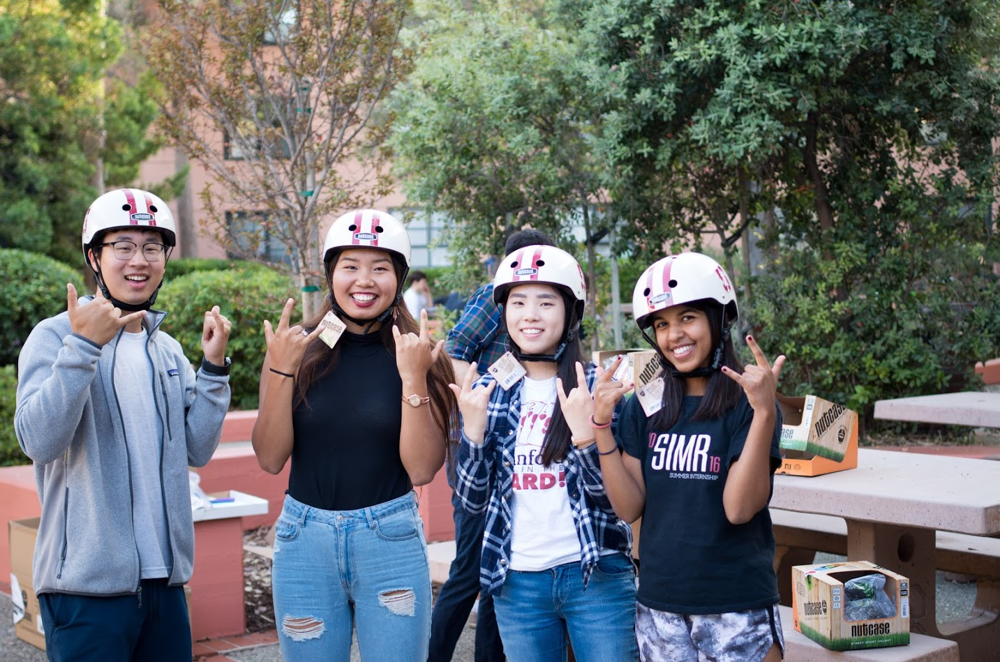 Four smiling students wearing bike helmets