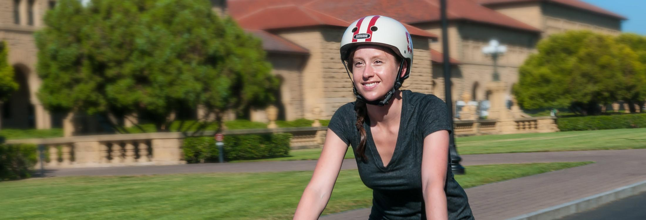 Smiling female cyclist wearing a Stanford-branded helmet riding on Serra Mall.