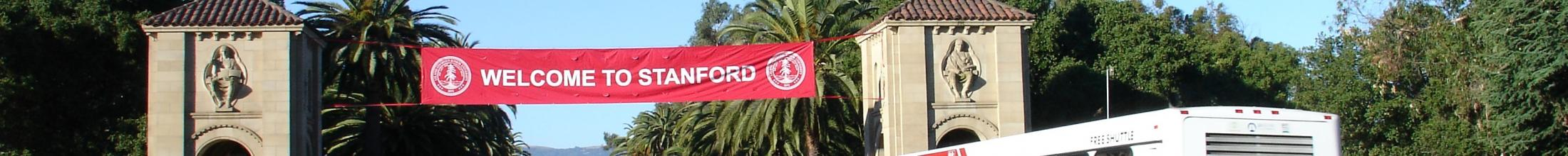 "Marguerite bus on Palm Drive below ""Welcome to Stanford"" banner"