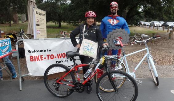 woman on Bike to Work day posing with Sprocket Man