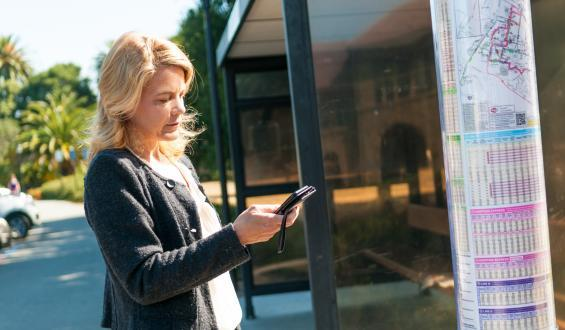 woman by transit stop looking on cell phone