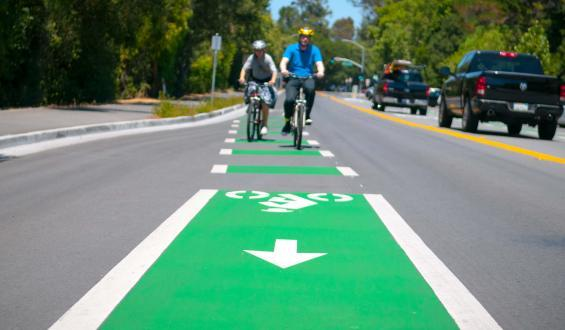Cyclists biking between the bike lanes
